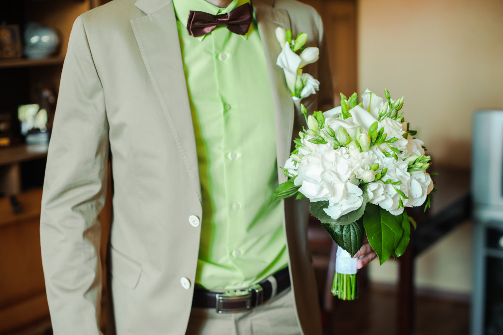 Groom in a green shirt with a wedding bouquet in his hands