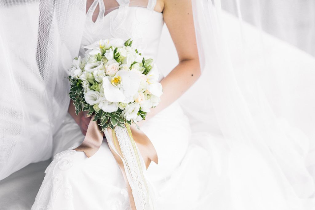 bride in a white wedding dress with white roses
