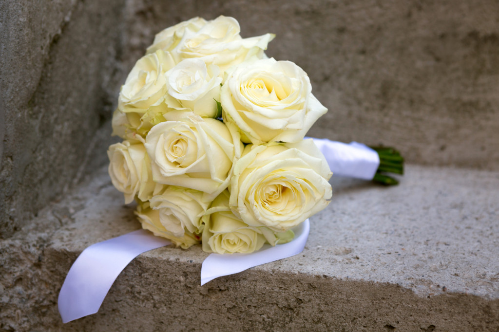 yellow wedding bouquet laid on a concrete stairs
